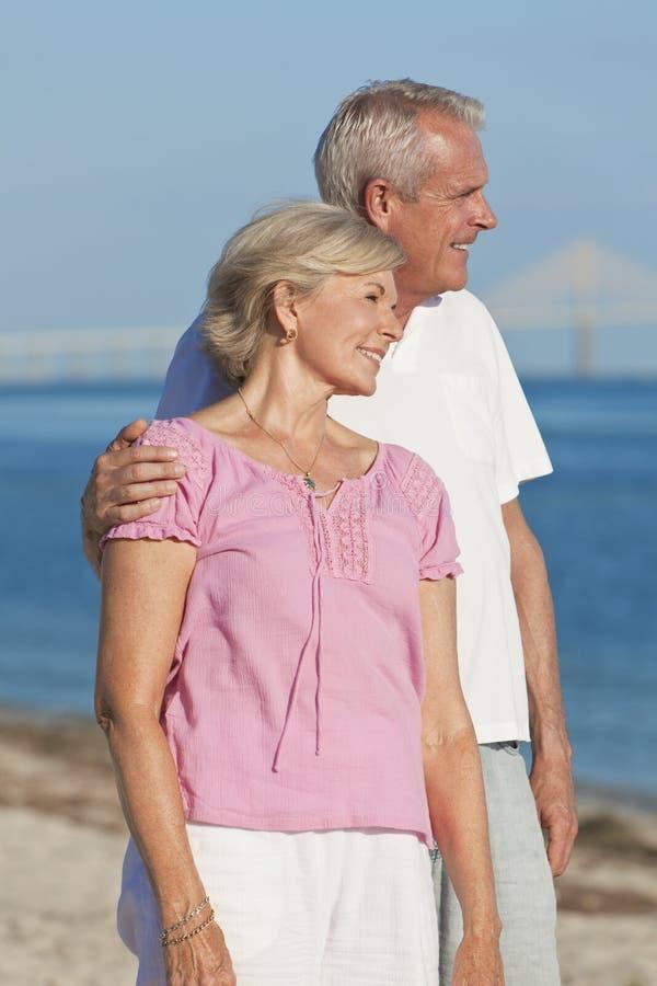 Lyckliga romantiska höga par som omfamnar på strand arkivfoton