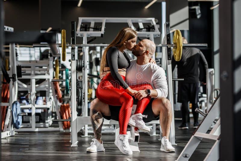 Lyckliga romantiska idrotts- par Den spensliga härliga flickan sitter på knä av den starka idrotts- mannen och att kyssa i fotografering för bildbyråer