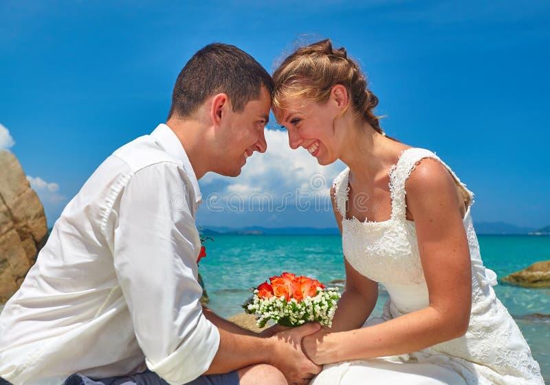 Lyckliga romantiska par, brudgum och brud i vit bröllopsklänningsi royaltyfri fotografi