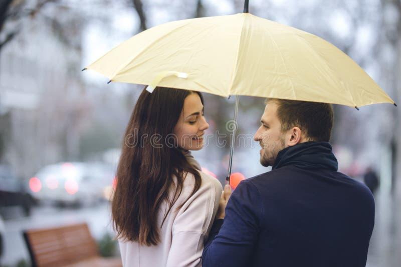 Lyckliga romantiska par, grabben och hans iklädda tillfälliga kläder för flickvän går under paraplyet och ser de royaltyfria foton