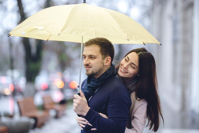 Lyckliga romantiska par, grabben och hans ikl?dda tillf?lliga kl?der f?r flickv?n kramar under paraplyet och ser varje arkivfoton