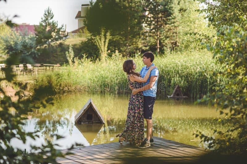 Lyckliga romantiska par i byn, promenad på träbron nära sjön Ungt härligt krama för kvinna och för man royaltyfri bild