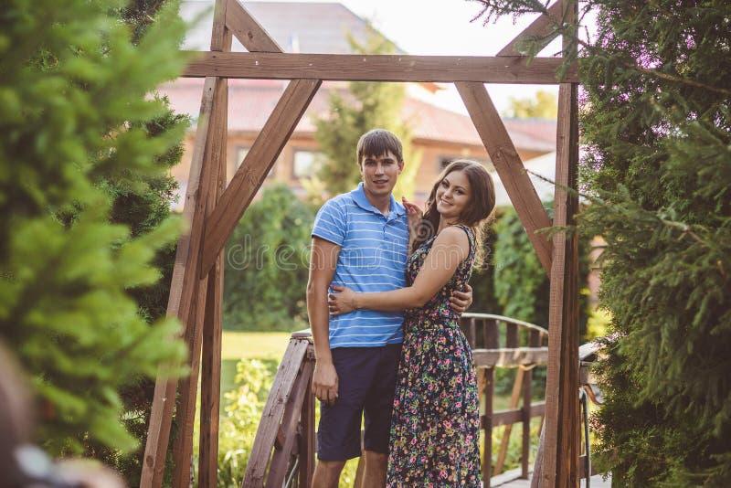 Lyckliga romantiska par i byn, promenad på träbron Ung härlig kvinna i långt krama för sommarklänning royaltyfria foton