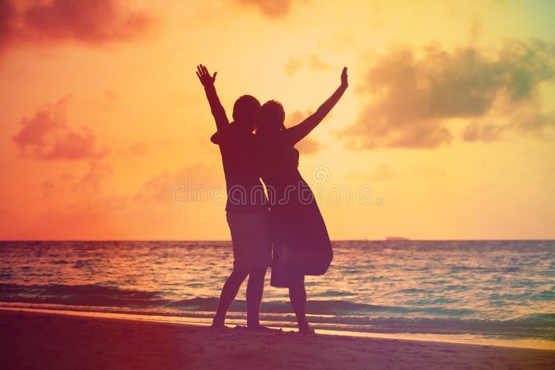 Lyckliga romantiska par på stranden på solnedgången royaltyfria bilder