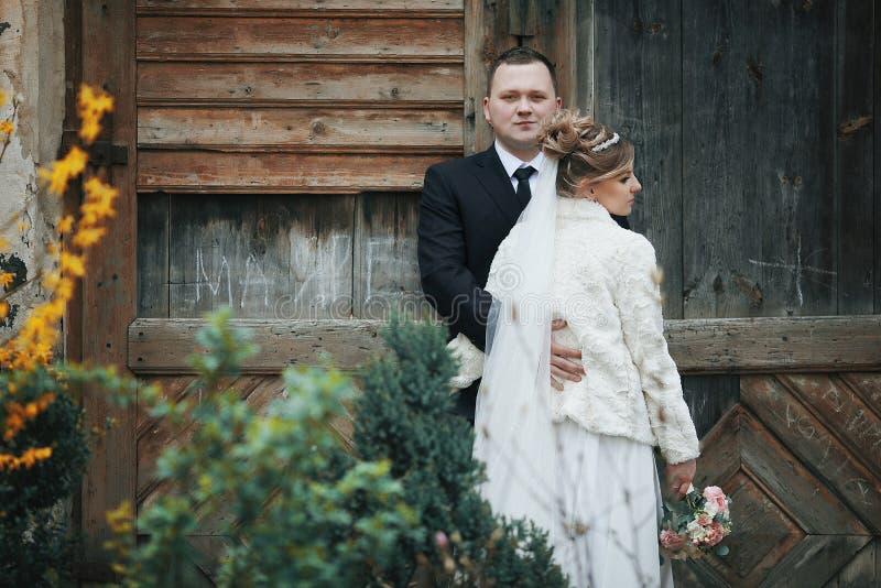 Lyckliga romantiska par som kramar nära den gamla träväggen royaltyfri fotografi
