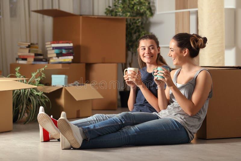 Lyckliga rumskamrater som flyttar hem att vila och samtal royaltyfri bild