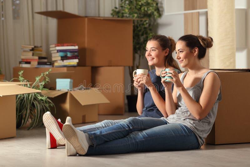 Lyckliga rumskamrater som flyttar hem- vila dricka kaffe royaltyfri foto