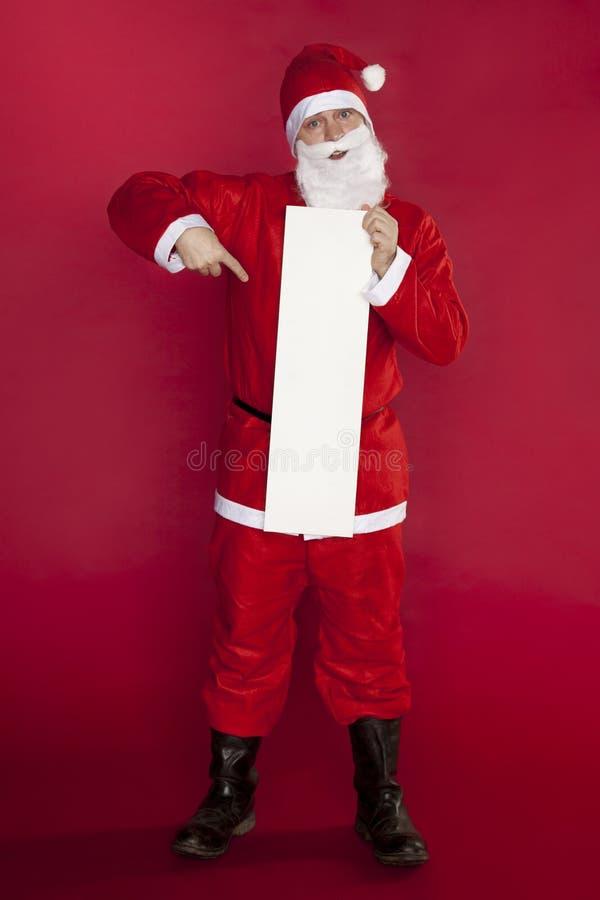 Lyckliga Santa Claus håller ett ställe för annonsering, kopieringsutrymme royaltyfri foto