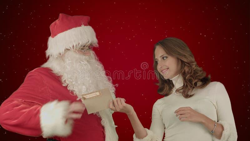 Lyckliga Santa Claus med hans läs- jul för kvinnahjälpredan märker eller önskelistan på röd bakgrund med snö royaltyfria foton