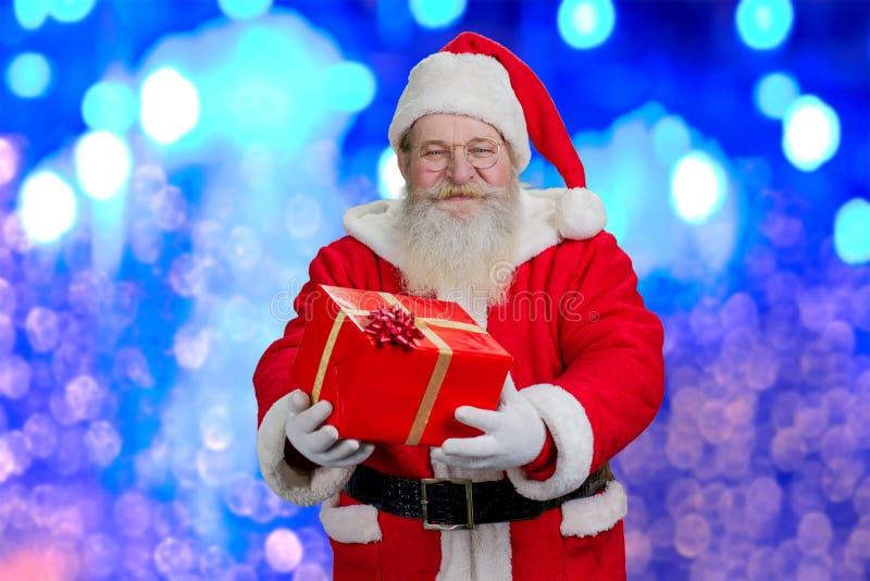 Lyckliga Santa Claus som rymmer den röda gåvaasken fotografering för bildbyråer