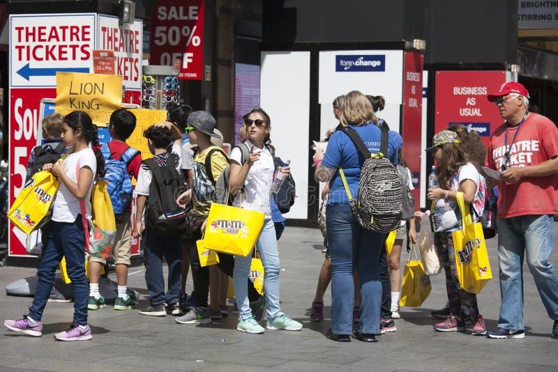 Lyckliga shoppare med gula paket av M royaltyfri foto