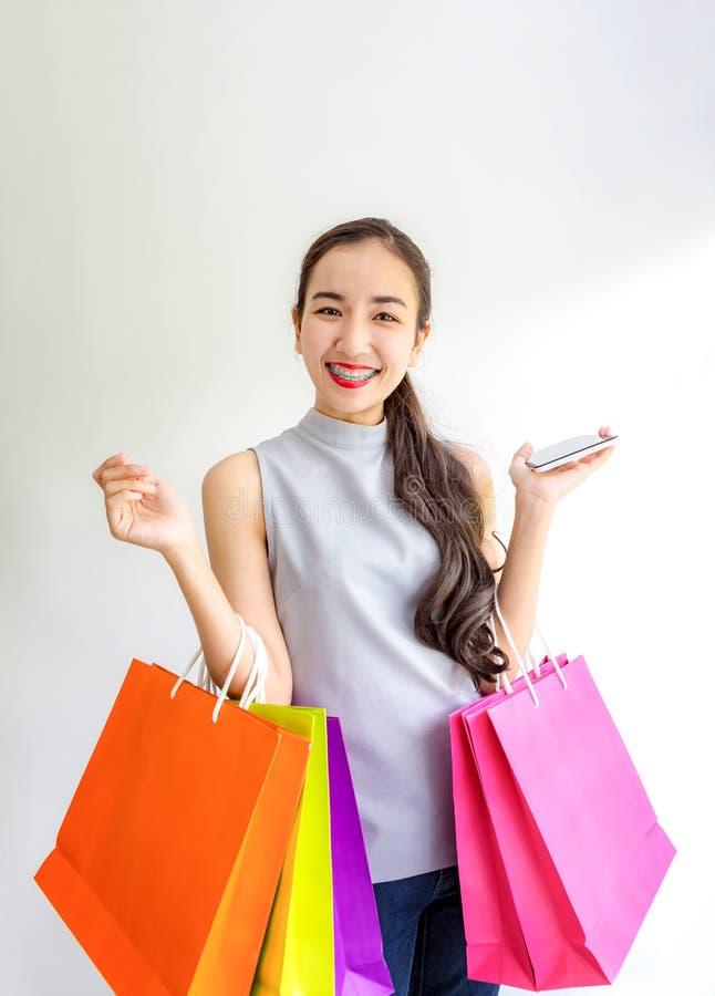 Lyckliga shoppingpåsar och mobiltelefon för ung kvinna hållande Gör online-shopping på en minnestavla Härligt asiatiskt bära för  royaltyfri bild