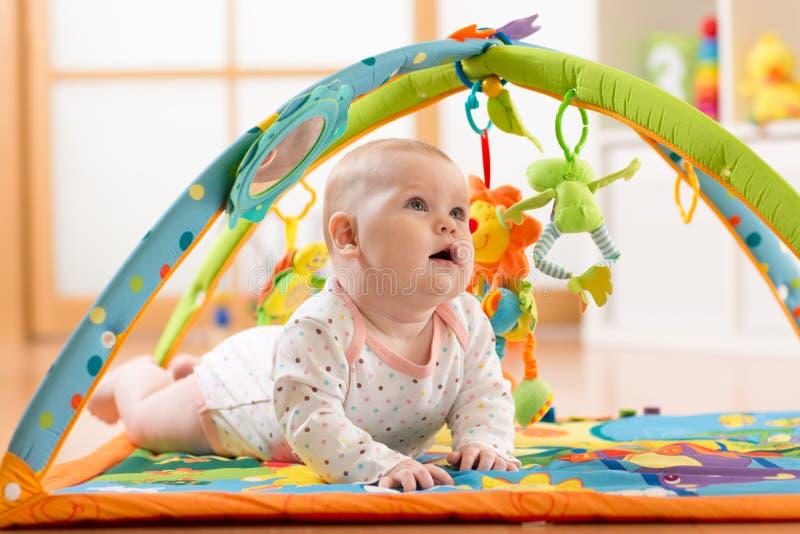 Lyckliga sju månader behandla som ett barn flickalekar som ligger på färgrik playmat royaltyfri foto