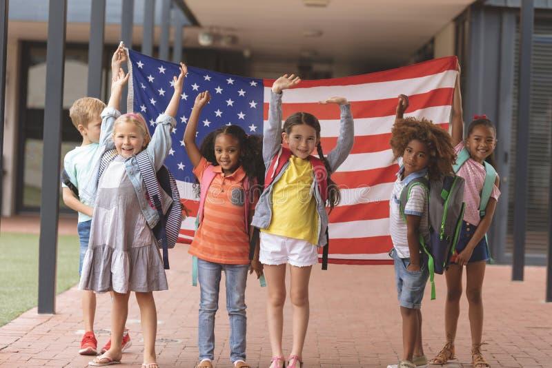 Lyckliga skolastudenter som står i korridor, medan rymma amerikanska flaggan arkivfoton