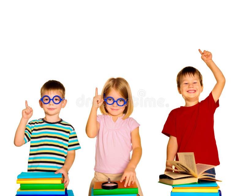 Lyckliga skolaungar som ler och pekar upp royaltyfria foton