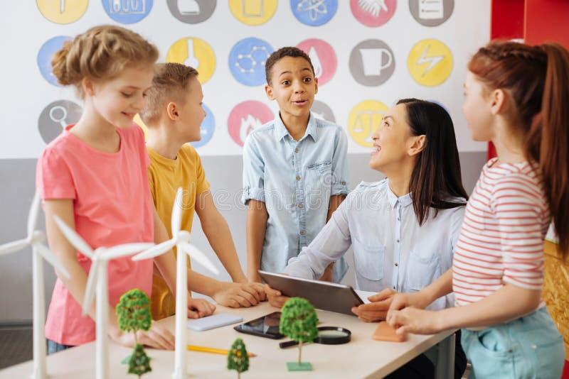 Lyckliga skolbarn som skojar med deras ekologilärare royaltyfri foto