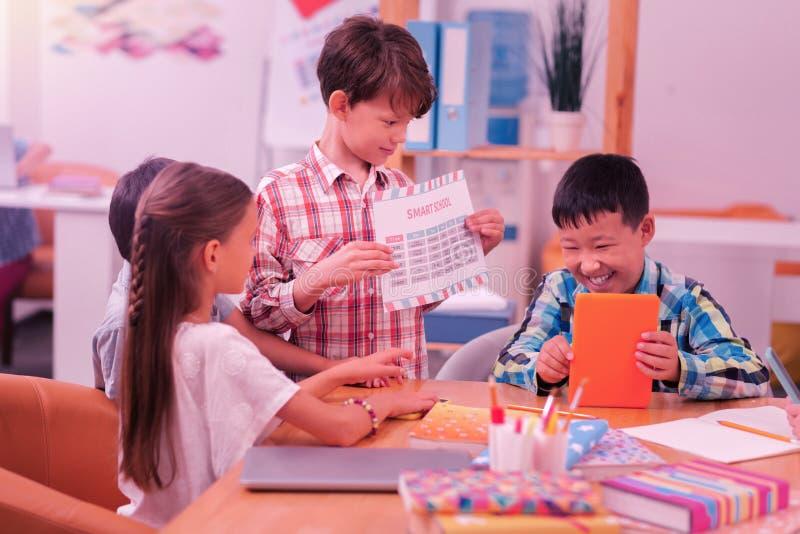 Lyckliga skolbarn som tillsammans sitter på skrivbordet arkivfoto