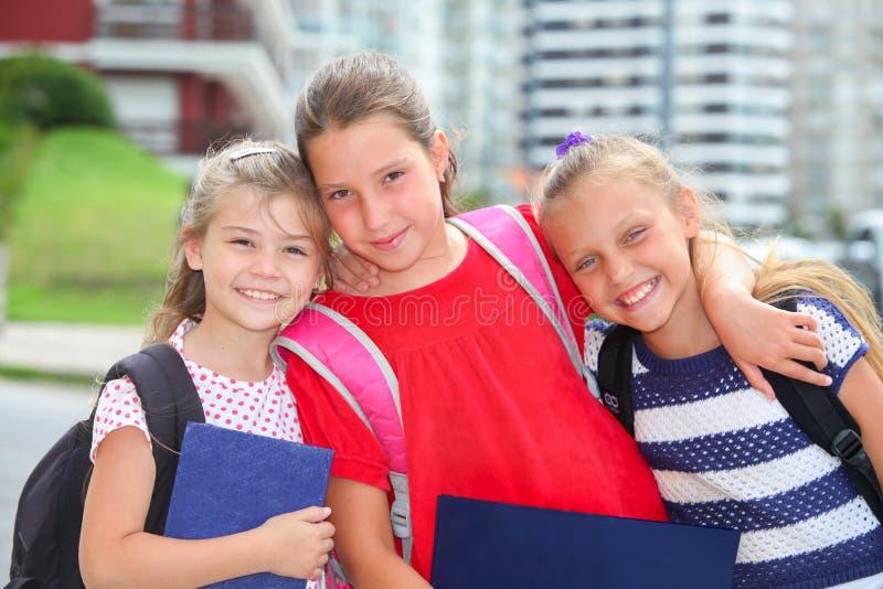 Lyckliga skolflickor med ryggsäckar fotografering för bildbyråer