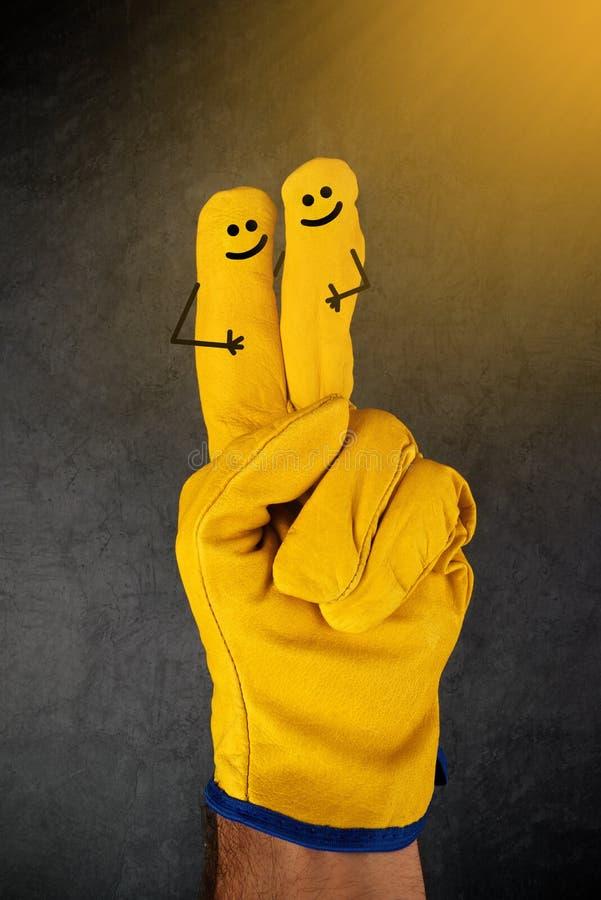 Lyckliga skratta Smileys på fingrar av skyddande handskar royaltyfria bilder