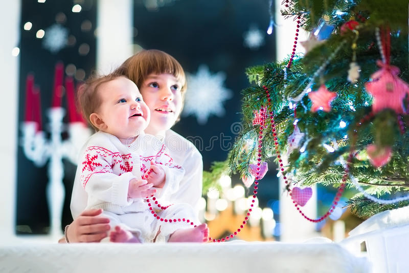 Lyckliga skratta ungar under en härlig julgran i en mörk vardagsrum royaltyfri foto