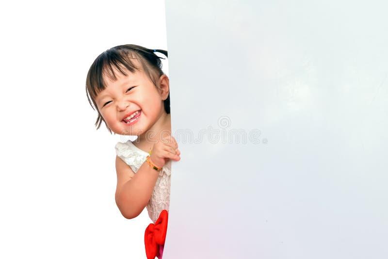 Lyckliga små asiatiska barn ler att kika ut bak bräde Utrymme för kopieringssammansättning för, websiten, tidskrift eller royaltyfria bilder