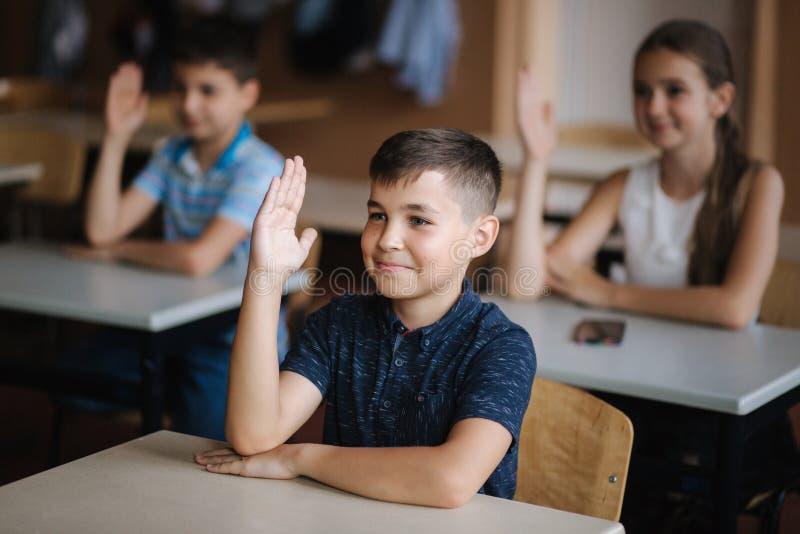 Lyckliga små barn i grundskola Pojkar och flickor studerar Barn lyfter upp handen royaltyfri foto