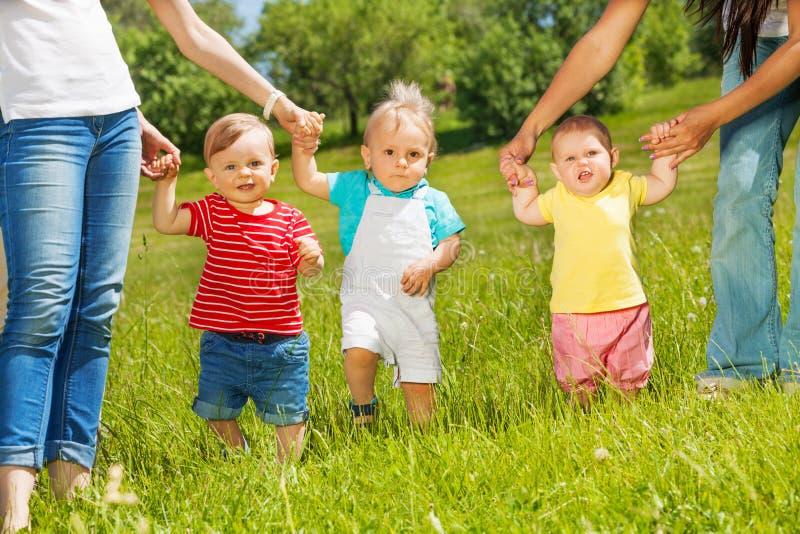 Lyckliga små barn lär att gå innehavmoderhänder royaltyfria foton