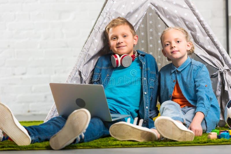 lyckliga små barn med bärbara datorn som ser kameran och sitter med tältet royaltyfria foton
