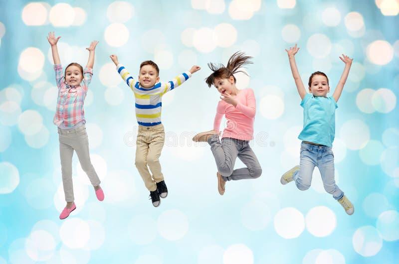 Lyckliga små barn som hoppar över blåa ljus royaltyfria foton