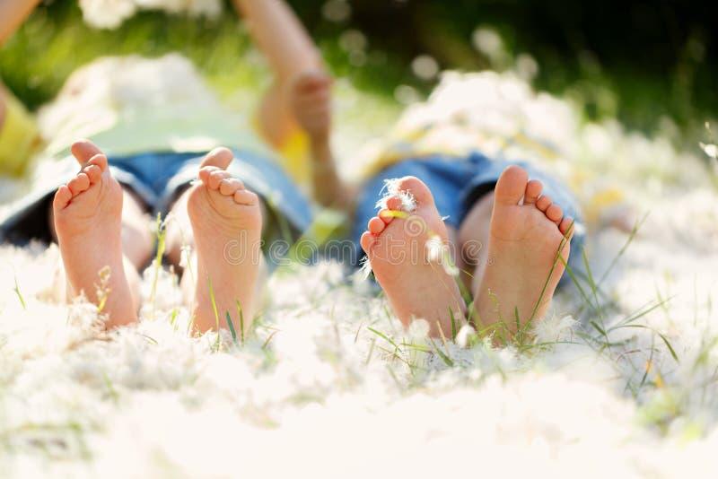 Lyckliga små barn som ligger i gräset med fjädrar, barefo arkivfoto