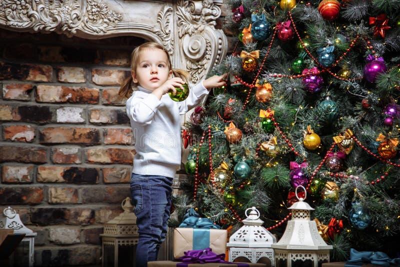 Lyckliga små behandla som ett barn flickan som dekorerar julträdet med leksaker på ferier fotografering för bildbyråer