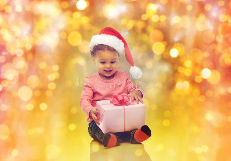 Lyckliga små behandla som ett barn flickan med julgåva royaltyfri bild