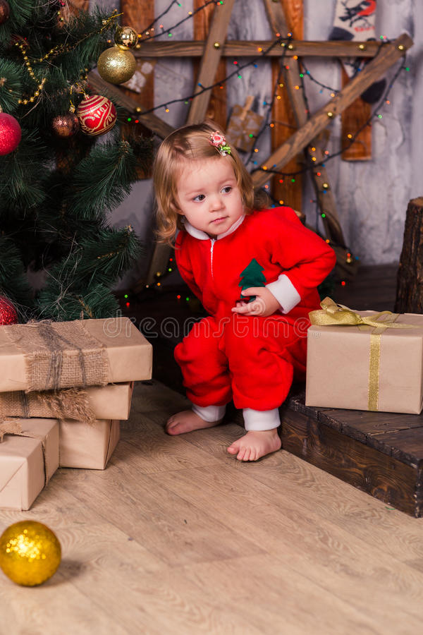 Lyckliga små behandla som ett barn i dräkt för jultomten` s nära Xmas-träd arkivfoton