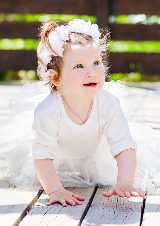 Lyckliga små behandla som ett barn i en smart klänning kryper royaltyfria bilder