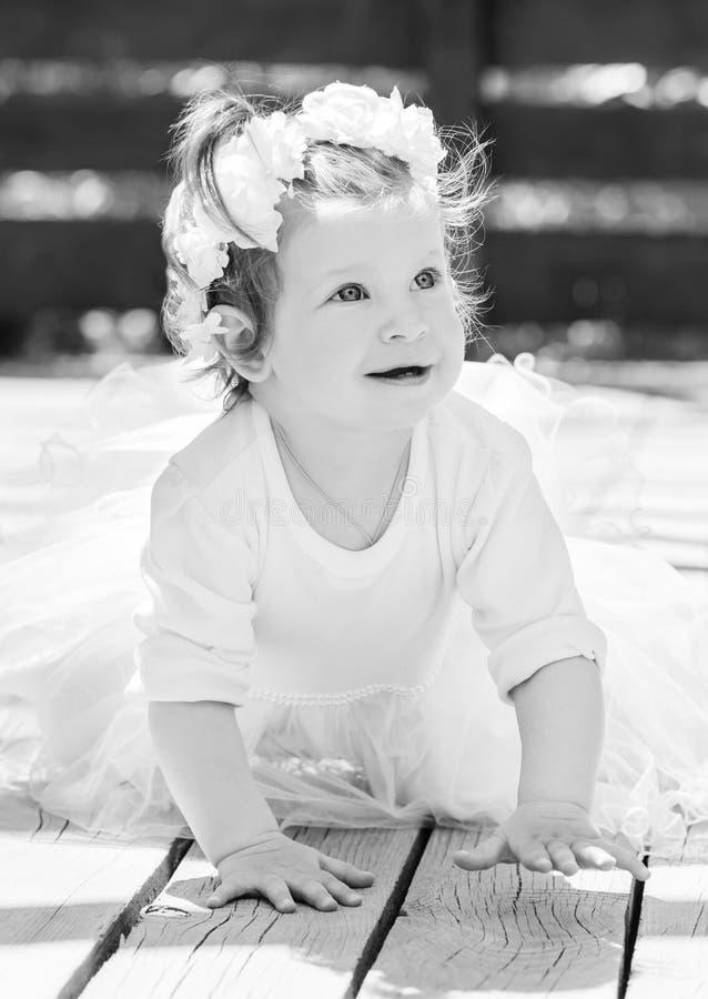 Lyckliga små behandla som ett barn i en smart klänning kryper arkivfoton