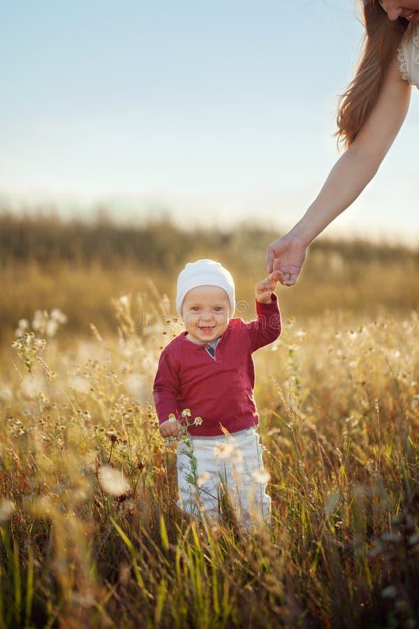 Lyckliga små behandla som ett barn pojkeanseende och att le på naturen i solig dag för sommar Barnet tar hans första steg fotografering för bildbyråer