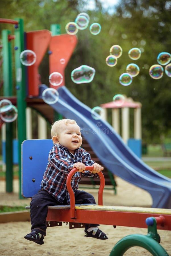 Lyckliga små behandla som ett barn pojken som spelar på lekplatsen i sommaren eller hösten royaltyfri fotografi