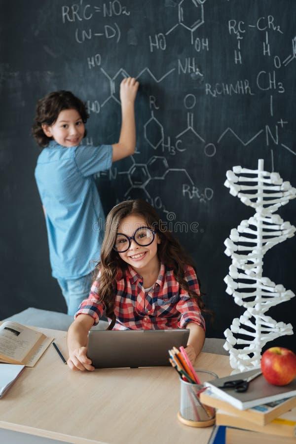 Lyckliga små elever som tycker om kemigrupp på skolan royaltyfri foto