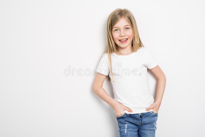 Lyckliga små fem år gammal flicka med rakt hår över vit bakgrund hemma royaltyfri bild