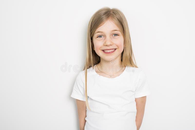 Lyckliga små fem år gammal flicka med rakt hår över vit bakgrund hemma royaltyfria foton
