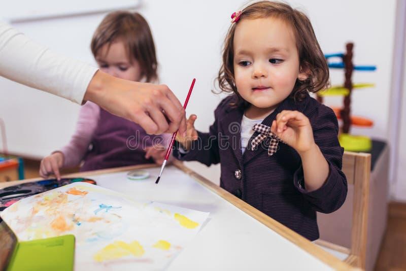 Lyckliga små flickor, förskolebarn, målning med vattenfärg, selektiv fokus royaltyfria foton