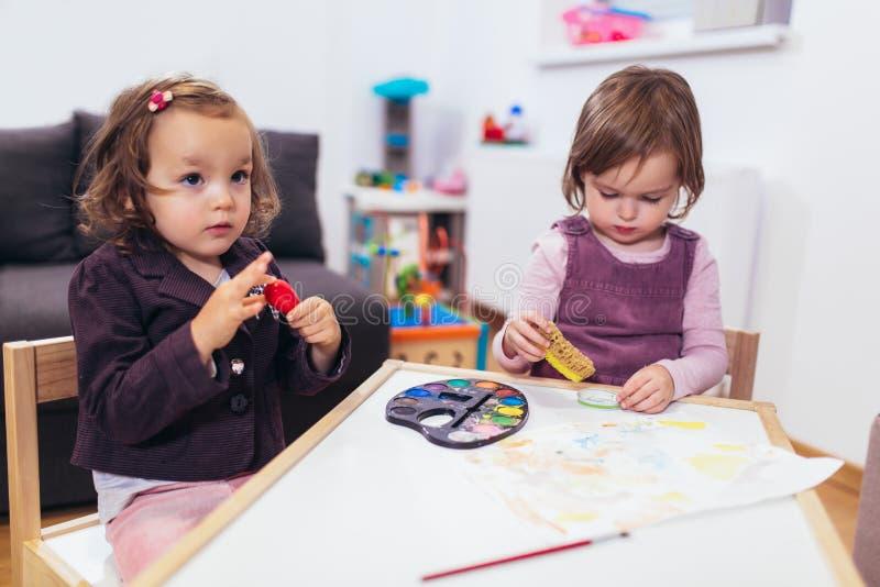 Lyckliga små flickor, förskolebarn, målning med vattenfärg, selektiv fokus arkivbild