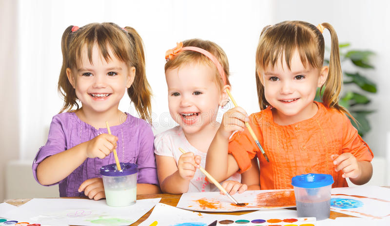 Lyckliga små flickor i dagisattraktionmålarfärger arkivfoto