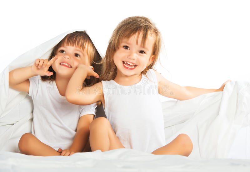 Lyckliga små flickor kopplar samman systern i säng under filten som den har royaltyfria foton