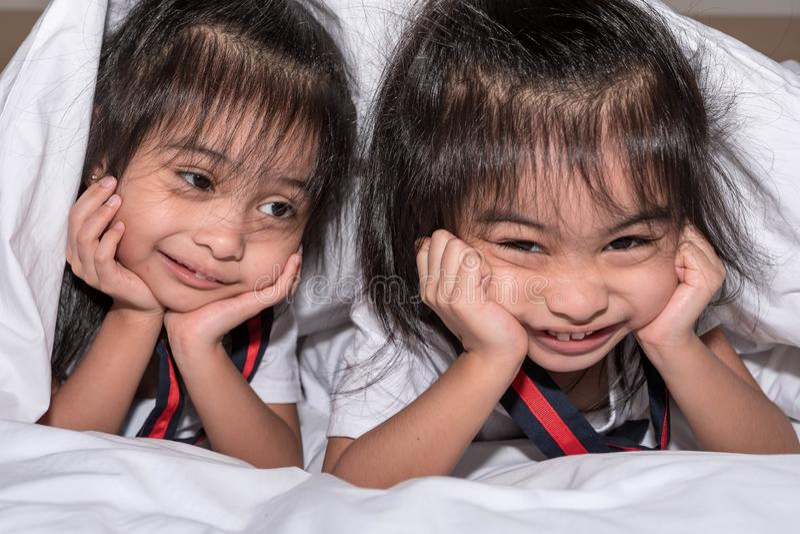 Lyckliga små flickor kopplar samman systern i säng under filten som har roligt och att le och knäpp royaltyfri foto