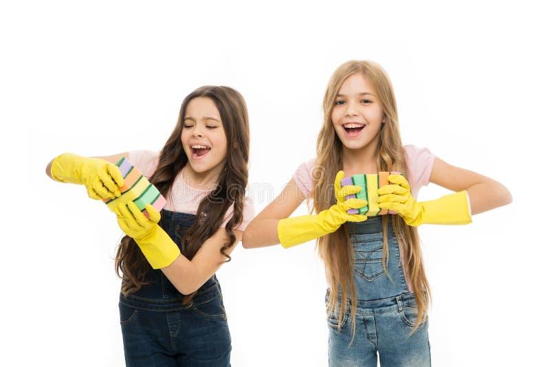 Lyckliga små flickor med den rengörande svampen Hush?llningarbetsuppgifter systrar tvättar disk som isoleras på vit Familjdag Hj? arkivfoton