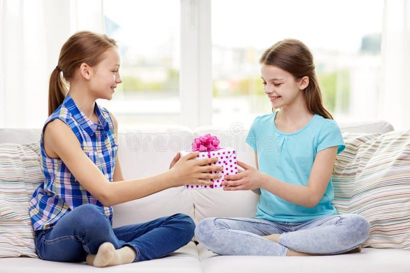 Lyckliga små flickor med födelsedaggåva hemma royaltyfri foto