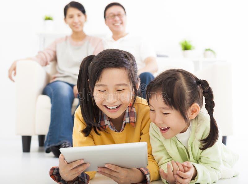 Lyckliga små flickor som använder minnestavlan arkivbild