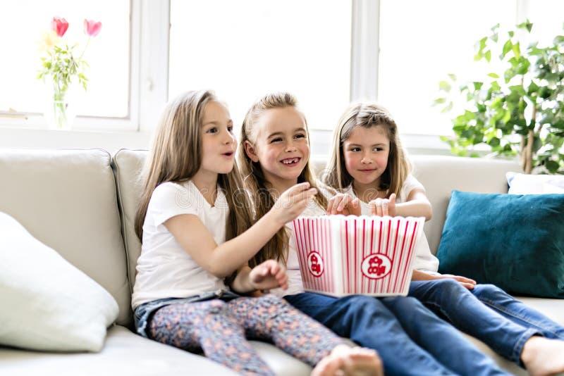 Lyckliga små flickor som håller ögonen på komedifilm på tv och hemma äter popcorn arkivfoto