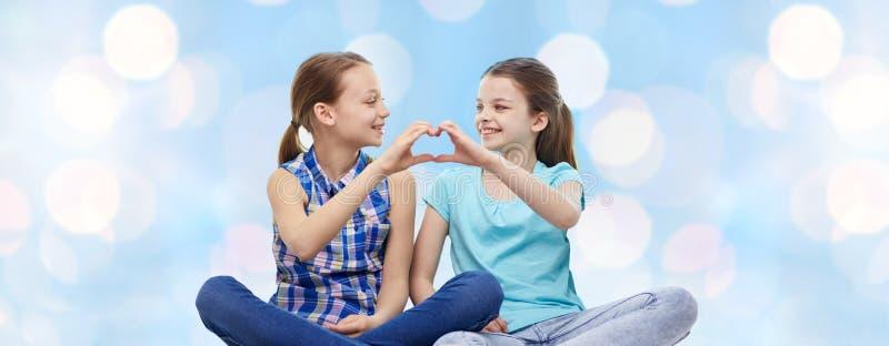 Lyckliga små flickor som visar tecknet för hjärtaformhand arkivbilder